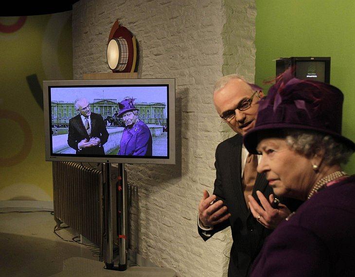 Метеоролог Франк Митчелл демонстрирует технологию зеленого экрана королеве Великобритании Елизавете II