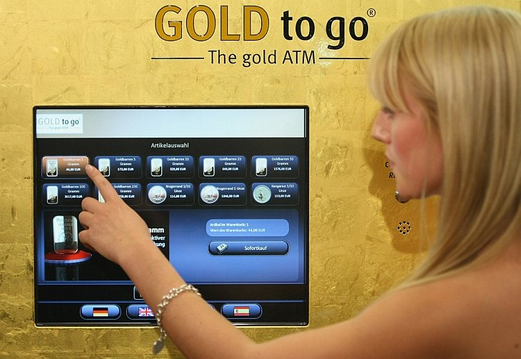 Девушка демонстрирует работу первого автомата по продаже золота Gold to go в Берлине