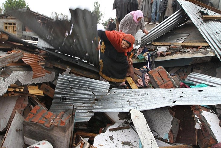 Мусульманские женщины спасают свои вещи под обломками домов после перестрелки на окраине города Сринагар, Индия