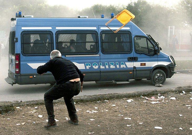 Протестующие забрасывают полицейскую машину различными предметами