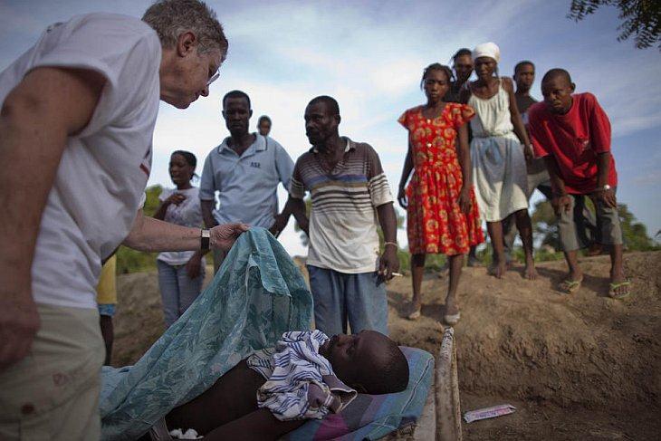 Люди смотрят на врача из США, который подтверждает, что человек умер от холеры