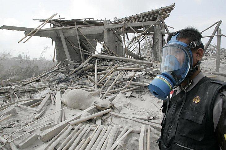 Спасатель стоит в деревне, пострадавшей от пирокластических потоков от извержения вулкана Мерапи