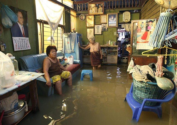Женщина сидит в своем затомленном доме в Бангкоке