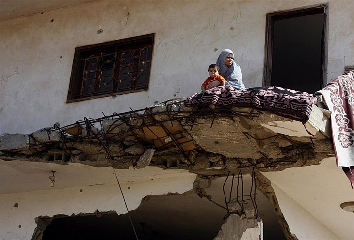 Палестинская женщина сидит с ребенком на руках на обломках своего дома