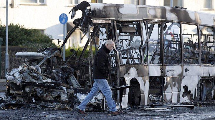 Человек идет мимо сгоревшего автобуса