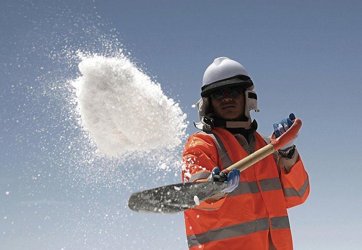 Работник бросает соль в соленое озеро Уюни