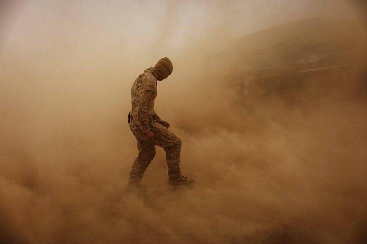 Рядовой 1-го класса 19-летний Брэндон Ворис из штата Огайо идет через песчаную бурю
