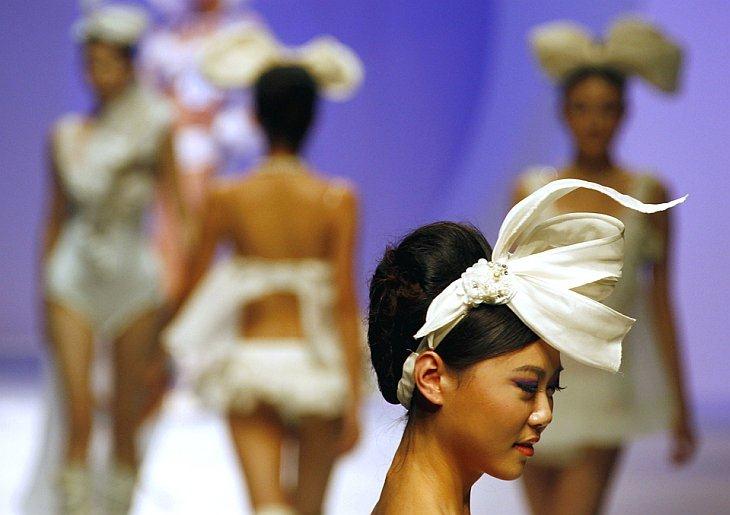 Модели идут по подиуму на конкурсе дизайна в рамках недели высокой моды в Китае