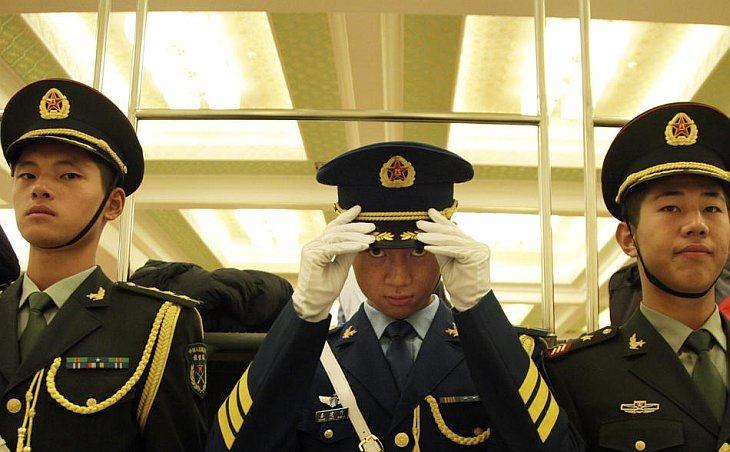 Член китайского почетного караула поправляет шляпу