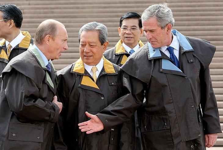 Президент США Джордж Буш (справа) протягивает руку, чтобы поприветствовать президента России Владимира Путина (слева)