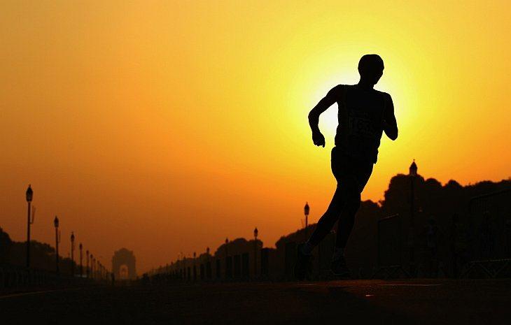 Спортсмен бежит мужской марафон на площади Виджай Чоук в 11-й день Игр Содружества в Дели, Индия