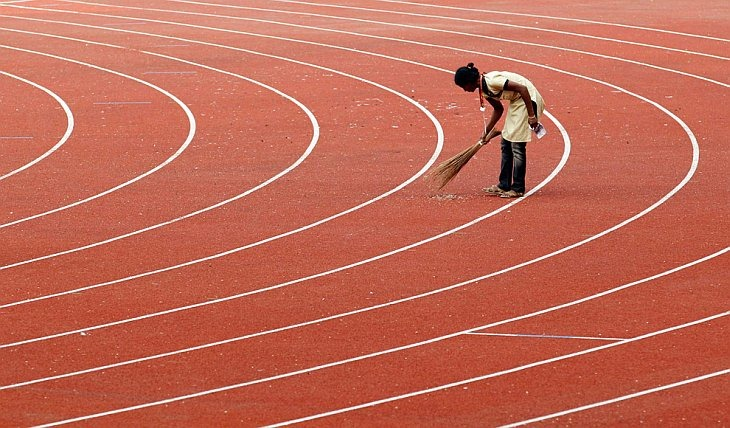 Работник подметает дорожки перед вечерней программой по легкой атлетике на стадионе Джавахарлала Неру во время Игр Содружества в Нью-Дели