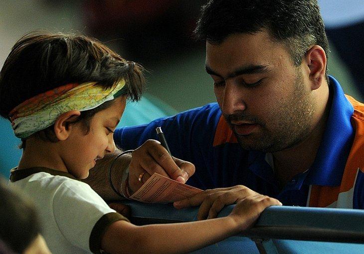 Индиец Гаран Наранг дает автограф молодому фанату