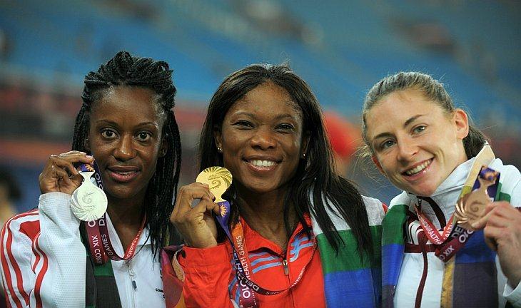 Слева направо, англичанка Абиодун Oyepitan (серебро), Cydonie Mothersill с Каймановых островов (золото) и канадка Адриенн Power (бронза) стоят на подиуме после женского финала по легкой атлетике в беге на 200м 11 октября 2010 в Нью-Дели