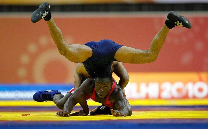 Азхар Хусейн из Пакистана (сверху) борется с Ембикевенимо Уэлсоном из Нигерии за золотую медаль