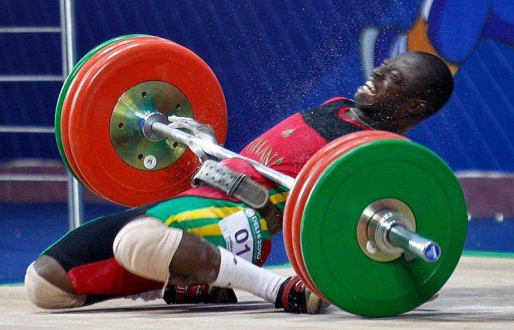 Seth Degbe Fetrie из Ганы придавлен штангой во время неудачной попытки подъема в соревновании по тяжелой атлетике в категории 69кг на Играх Содружества в Нью-Дели 6 октября 2010 года