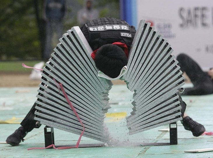 Южнокорейский полицейский разбивает головой каменные плиты