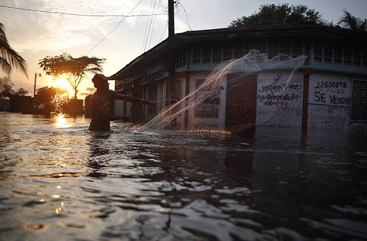 Рыбак бросает сеть на затопленной улице в Типитапа