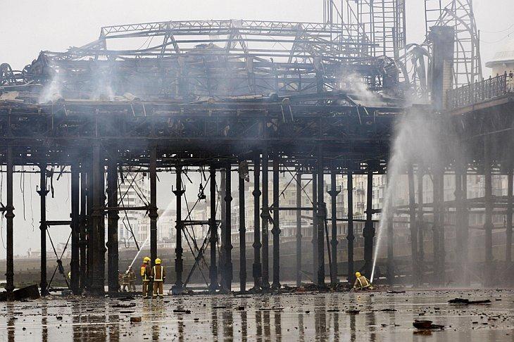 Пожарные поливают водой тлеющий пирс
