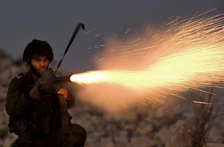 Израильский солдат поджигает слезоточивый газ