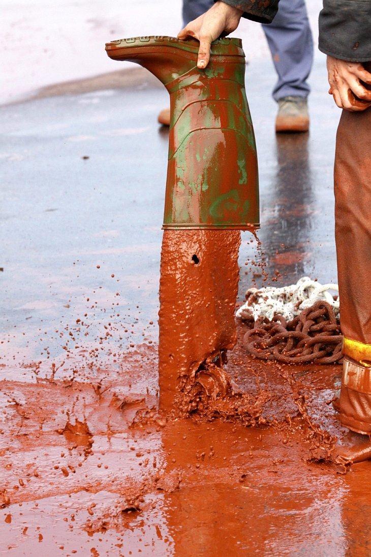 Пожарный выливает грязь из сапога в Дечевере